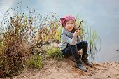 cute child girl in pink knitted hat plays with stick on sand river side