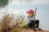 adorable child girl in pink knitted hat plays with stick on river side