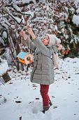cute child girl hanging bird feeder to the tree in winter snowy garden