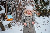 adorable child girl with seeds and bird feeder in winter snowy garden
