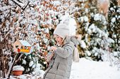 adorable child girl puts seeds in bird feeder in winter snowy garden