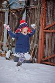 cute happy child girl in christmas hat on the walk in winter snowy garden