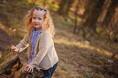 picture of early spring  - adorable smiling blonde child girl in blue shirt on the walk in early spring forest - JPG