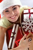 Happy girl on santa hat with gift box on red background