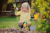 beauty child girl plays little gardener and planting flowers in spring garden