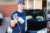 Car body repairer holding a spray gun