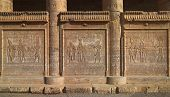 Hieroglyphic carvings on the exterior walls of an ancient egyptian temple