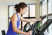picture of elliptical  - Yiung woman doing exercises with elliptical trainer in gym - JPG