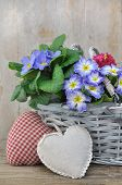 foto of wooden basket  - pansies in a basket with a hearts shaped cushion on a wooden background - JPG