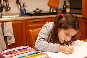 Pretty Girl Writes With Pencil Her Homework In The Kitchen