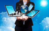Businesswoman holds modern technology in hands. Sky background - Stock Image