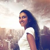 Pretty young Indian woman looking up into the air with a smile against a city background with modern skyscrapers and dramatic sky, square format conceptual of tourism and travel