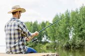 Young guy in hat sitting on bridge and fishing