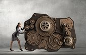 Attractive businesswoman pushing with effort working gears mechanism