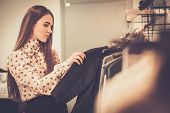 picture of racks  - Young woman choosing clothes on a rack in a showroom  - JPG