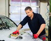 Man worker washing luxury car with sponge on a car wash