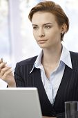 Portrait of young attractive businesswoman working with computer, looking away.