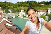 Travel selfie by woman in Bern Switzerland. Happy smiling multiracial Asian Caucasian girl taking self portrait photograph sitting on Nydeggbrucke by Aare river in the Swiss city of Bern.