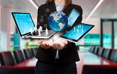 Businesswoman holds modern technology in hands. Office background - Stock Image