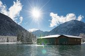 sun over boat house at sunny and snowy winter day in austria