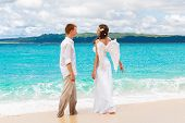 The Groom And A Beautiful Young Bride With Angel Wings On The Sea Coast.