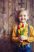 Little boy with bunch of red and yellow tulips looking at camera