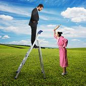 aggressive woman with rolling pin screaming and looking at dissatisfied man on stepladder. photo at outdoor