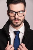 Close up picture of a elegant business man wearing glasses. He is fixing his coat while looking at the camera.