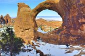 Female Hiker Climbing Up The Double-o-arch In Devil's Garden In Arches National Park, Utah In Winter