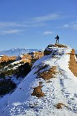 Hiker On Top Of The Mountain In Arches National Park, Utah In Winter
