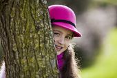 Beautiful child peeking behind a tree