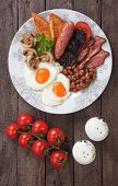 Full english breakfast with fried eggs, bacon, mushrooms, sausage and kidney beans