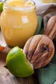pic of lime  - Lime with wooden juicer and homemade lime curd in glass jar on old wooden background - JPG