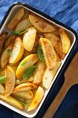 picture of baked potato  - baked potato wedges in enamel baking dish - JPG