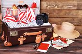 picture of packing  - Packed suitcase of vacation items on wooden background - JPG