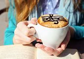 image of clefs  - Hands holding cup of cappuccino with treble clef on foam - JPG