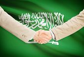 picture of saudi arabia  - Businessmen shaking hands with flag on background  - JPG