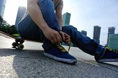 foto of skate board  - young skateboarder tying shoelace at skate park - JPG