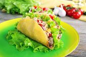 image of tacos  - Tasty taco on plate with vegetables on table close up - JPG
