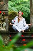 foto of tranquil  - Young woman doing yoga outdoors in tranquil environment - JPG
