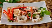 picture of squid  - hot and spicy stir fried squid with basil leaf on plate with rattan background - JPG