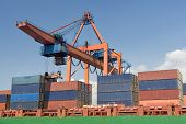 stock photo of loading dock  - Crane Loading Cargo on A Freight Ship - JPG