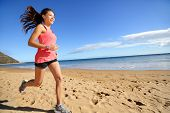 image of biracial  - Sports athlete runner running woman on beach sweating and jogging - JPG