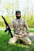 picture of rifle  - Bearded soldier with a rifle in the woods - JPG