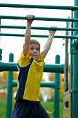 stock photo of swingset  - young boy concentrating on crossing monkey bars - JPG