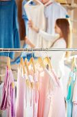pic of blouse  - Collection of new blouses in boutique with shopper on background - JPG