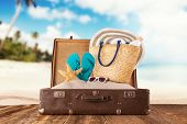 pic of mole  - Travel concept with old suitcase on wooden planks full of beach accessories - JPG