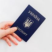 stock photo of passport cover  - an image of Ukrainian passport in hand on a white background - JPG