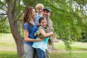 foto of reunited  - Handsome soldier reunited with family on a sunny day - JPG