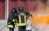 pic of fire brigade  - two firefighters in action with foam to put out the fire of the car - JPG